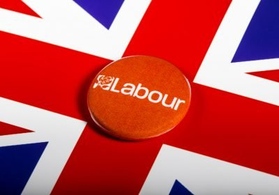 A Labour Party pin badge over the UK flag