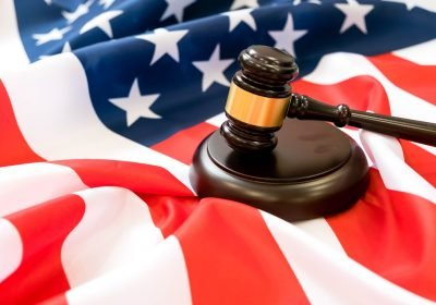 Wooden judge gavel and soundboard laying over US flag
