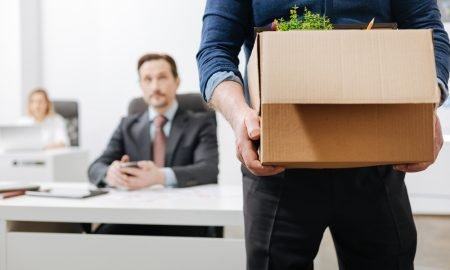 man leaving office with box of his things