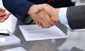businessmen shaking hands over contract